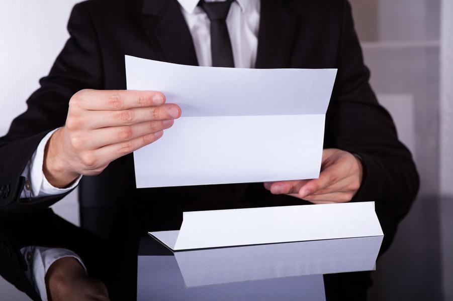 Мужчина держит в руке документы
