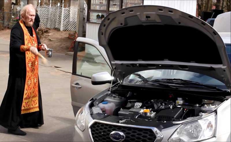 Батюшка освящает автомобиль